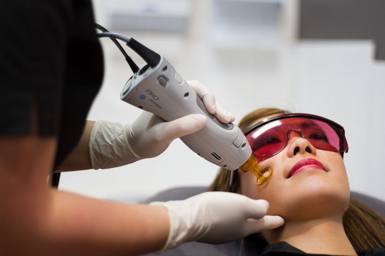 خانمی با عینک دودی با شیشه قرمز روی تخت دراز کشیده و خانمی دیگر در حال لیزر موهای زائد صورت اوست
