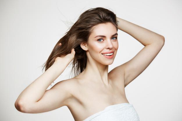 دختری زیبای مو قهوه ای که لبخند به لب دارد و یکی از دست های خود را بین موهایش برده و یکی از دستانش پشت سرش است
