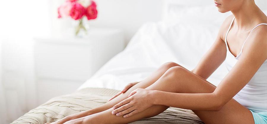 خانمی لاغر اندام که تاپ سفیدی به تن دارد روی تخت در حالی نشسته که زانوهای خود را به بالا خم و پاهایش را با دست هایش گرفته