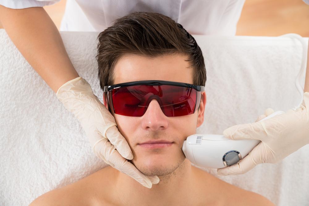 مردی عینکی دودی با شیشه قرمز زده و روی تخت خوابیده و خانمی دست راستش را روی صورتش گذاشته با دست چپ در حال لیزر موهای زائد صورت کنار لب او است